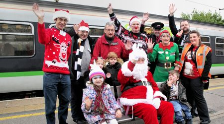 Santa, staff and volunteers sitting in front of a train carriage
