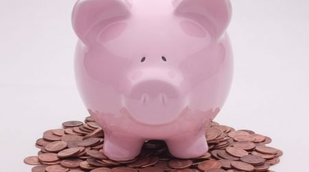 Piggy bank sitting on a pile of pennies