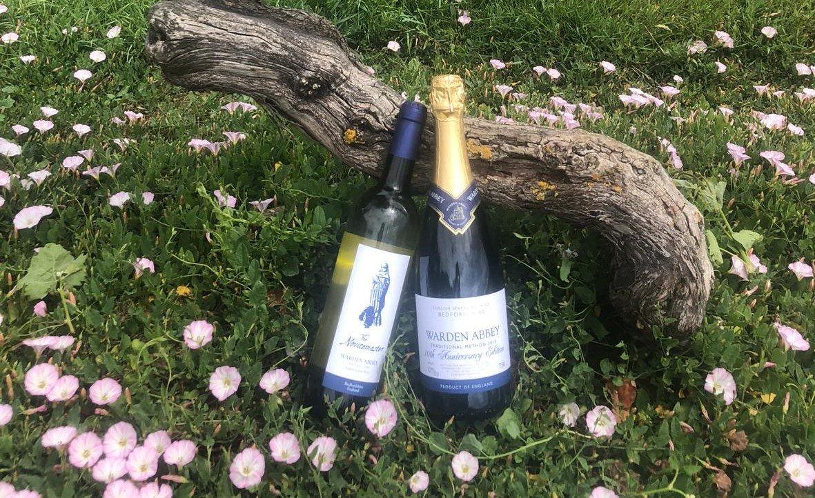 Two bottles of Warden Abbey Vineyard wine sitting in wildflowers