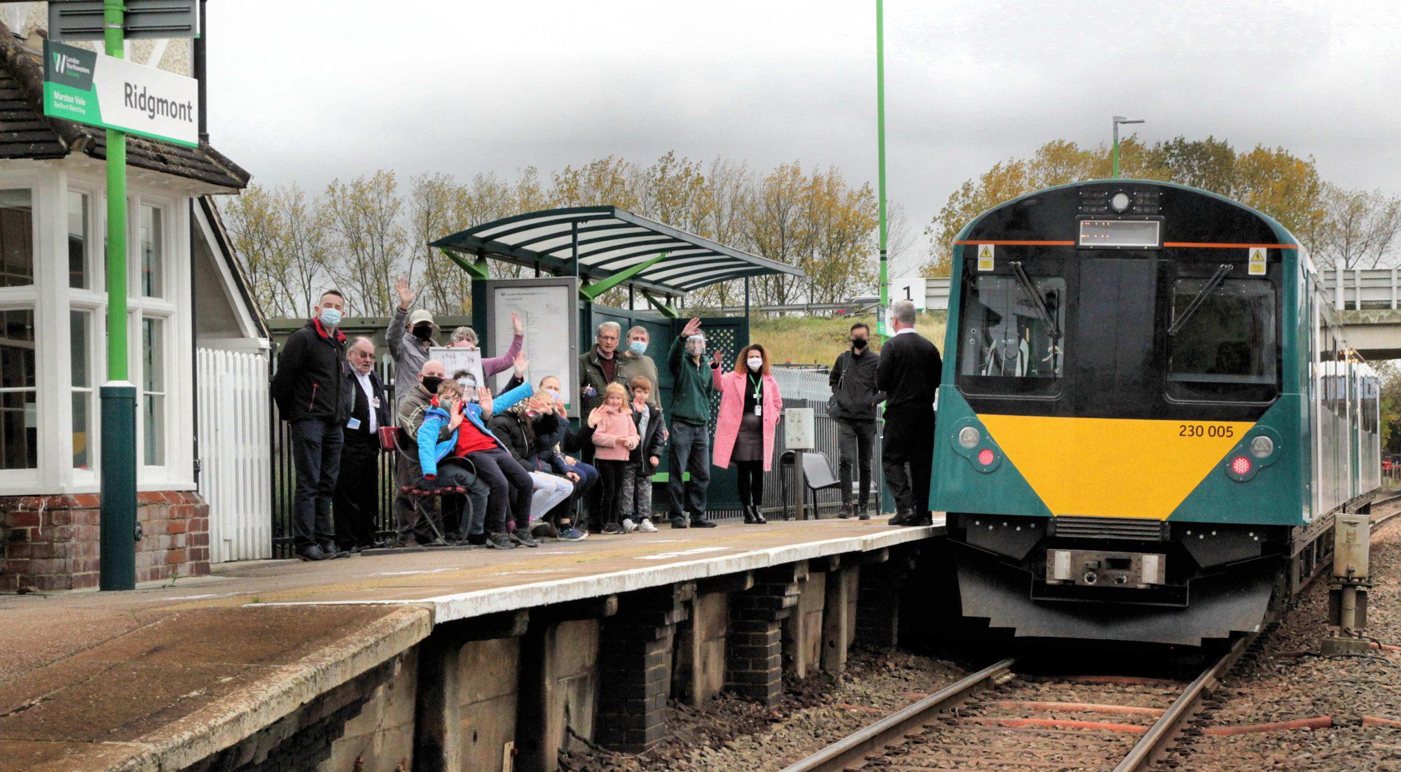 Passengers at station platform with train