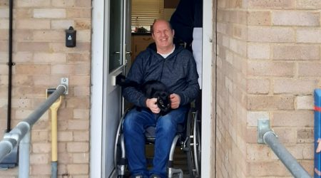 Smiling man in a wheelchair holding a cat