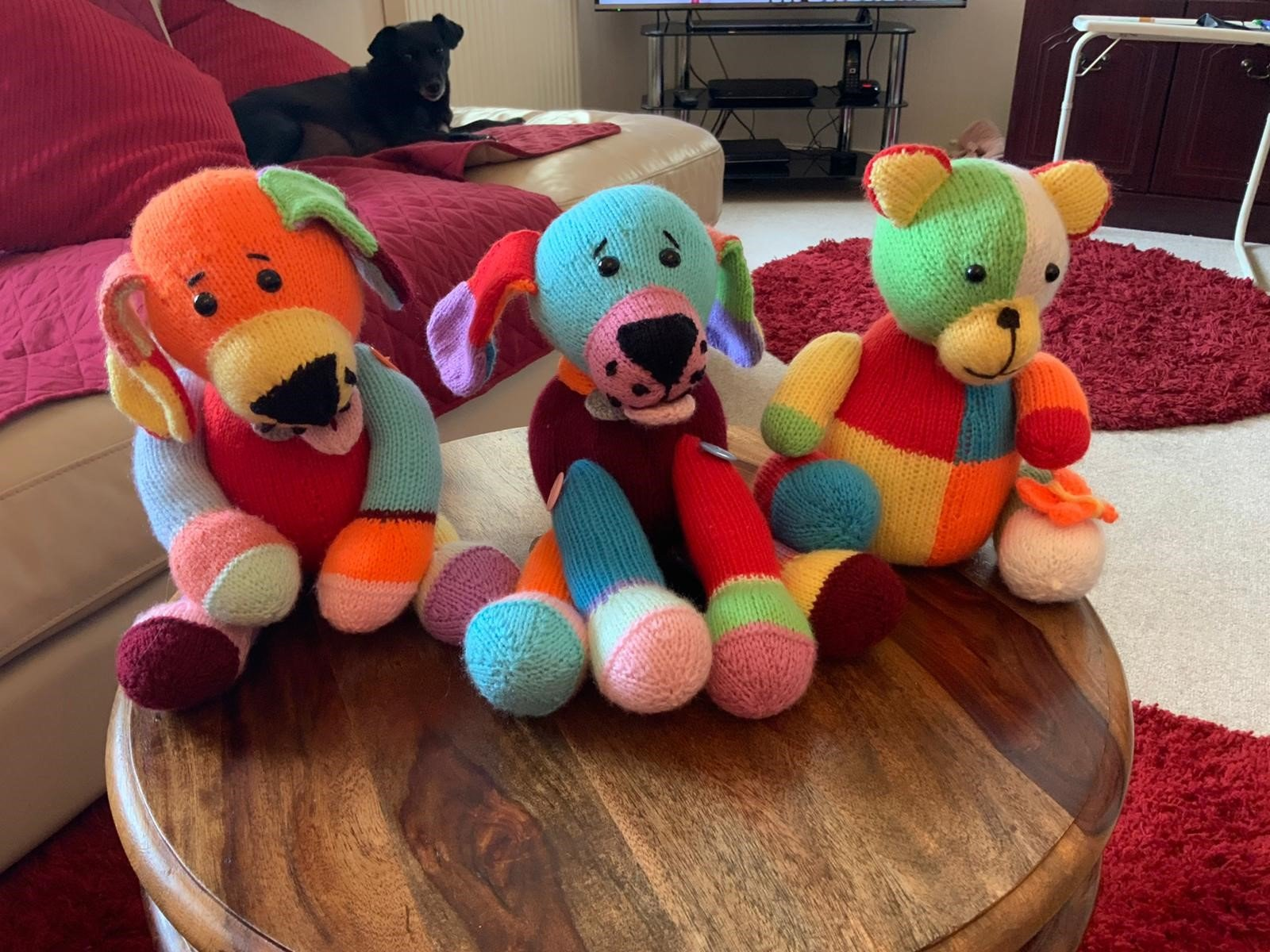 3 Knitted teady bears sitting on coffee table